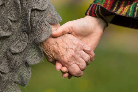 elderly adults: Holding hands together - old and young, close-up outdoors. Stock Photo