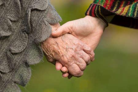 Tomados de la mano juntos - viejos y jóvenes, primer plano al aire libre. Foto de archivo