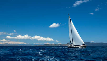 sailing boat: Ship yachts with white sails in the open Sea. Sailing luxury boats.