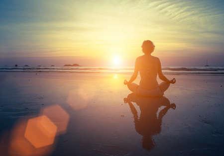 vida sana: Yoga, fitness y estilo de vida saludable. Muchacha de la silueta de la meditación en el fondo de la vista panorámica al mar y la puesta de sol. Mujer que hace la meditación cerca del océano. Silueta de la yoga. Foto de archivo