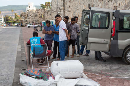 middle east crisis: KOS, GREECE - SEP 27, 2015: War refugees are registered by employees of the UNHCR. Kos island is located just 4 kilometers from the Turkish coast, and refugees come from Turkey on inflatable boats.