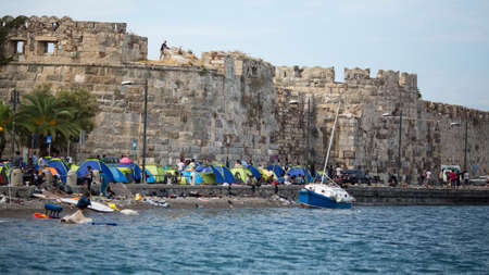 KOS, GREECE - SEP 28, 2015: Tents war refugees in the port of Kos island. Kos island is located just 4 kilometers from the Turkish coast, and many refugees come from Turkey in an inflatable boats. Редакционное