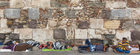 kos: KOS, GREECE - SEP 27, 2015: Refugees sleeping on the ground along the stone wall. Kos island is located just 4 km. from the Turkish coast, and many refugees come from Turkey in an inflatable boats.