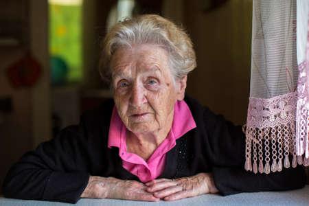 Portrait d'une femme âgée assise à la table de la maison. Banque d'images - 46344887