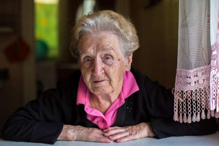 Portrait of elderly woman sitting at the table of the house.