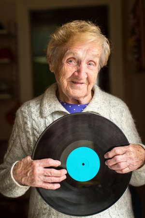 lp: Old woman holding an old LP vinyl record.