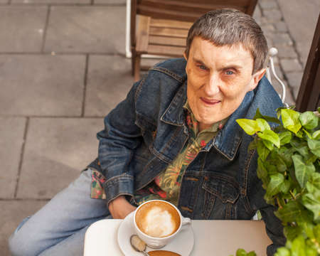 cerebral palsy: Disabled man with cerebral palsy sitting an outdoor cafe. Stock Photo