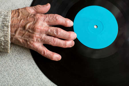 senile: Senile hand is on vinyl LP. Close-up of the old man or old woman hand. Space for your text.