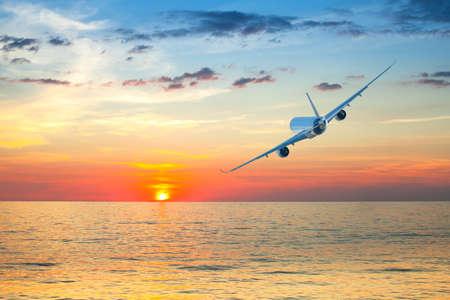 jumbo jet: Jumbo jet airplane flying above tropical sea at beautiful sunset.