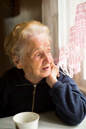 vejez feliz: Una señora mayor se sienta cerca de la ventana de la cocina. Foto de archivo