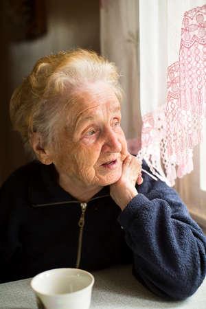 vecchiaia: Una signora anziana seduta vicino alla finestra della cucina.