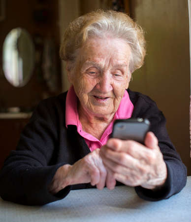 Elderly woman typing on the smartphone. Grandma. Banque d'images