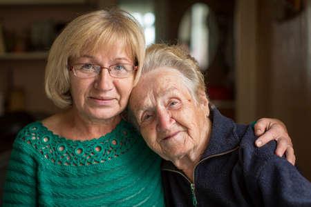persona de la tercera edad: Retrato de una mujer mayor con su hija adulta.