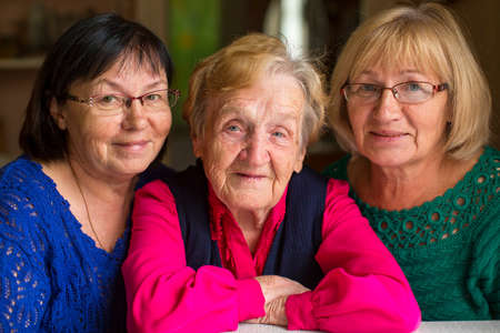 old people group: Elderly woman with two adult daughters.