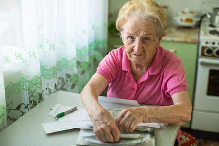 utility payments: Elderly woman with bills to pay utilities.