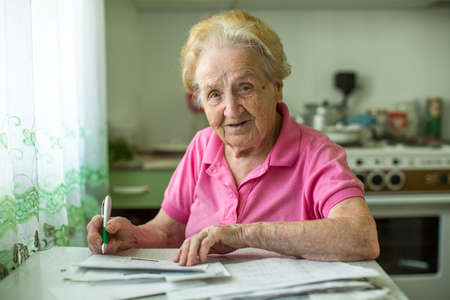 calculated: An elderly woman fills the bill for utilities sitting in the kitchen. Stock Photo