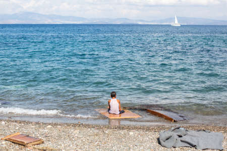 KOS, GREECE - SEP 27, 2015: Unidentified refugee on a beach. Kos island is located just 4 kilometers from the Turkish coast and refugees come from Turkey in an boat.