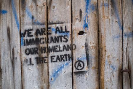 bateau: Kos, Gr�ce - 28 septembre 2015: Stencil sur le mur: Nous sommes tous des immigrants, notre patrie toute la terre. Kos est situ� � seulement 4 km de la c�te turque, et beaucoup de r�fugi�s sont originaires de Turquie dans un des bateaux.