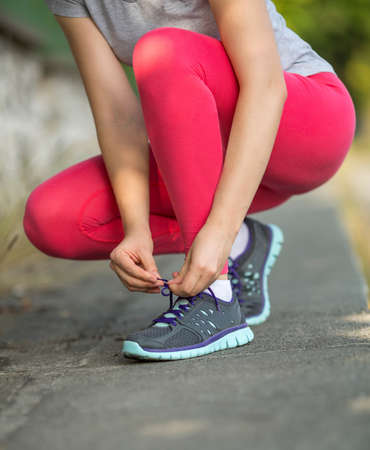 lacing sneakers: Sports girl ties the laces on sneakers, outdoors, close-up. Stock Photo