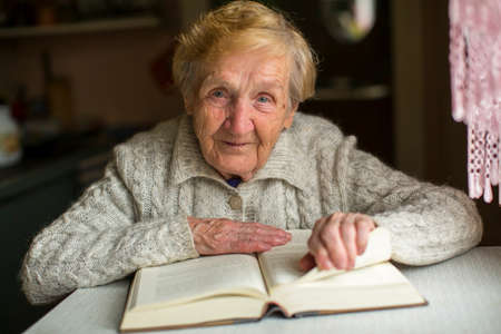 Old woman reading a book sitting at the table.