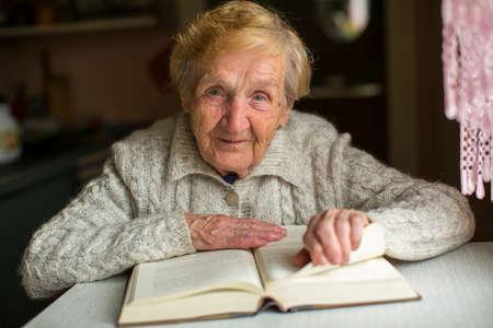 Alte Frau mit einem Buch am Tisch sitzen zu lesen. Standard-Bild