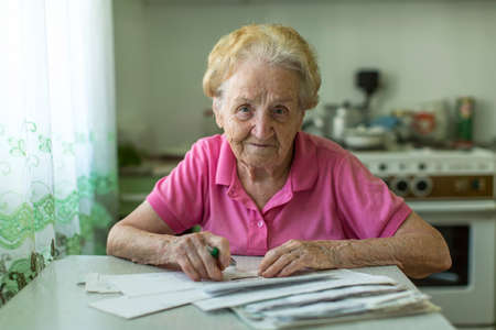 elderly adults: An elderly woman fills the bill for utilities sitting at the table in the kitchen.