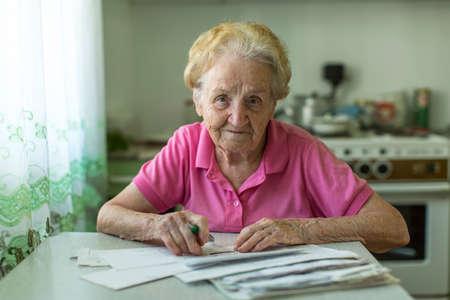 cuenta: Una mujer mayor llena la factura por los servicios públicos que se sientan en la mesa de la cocina.