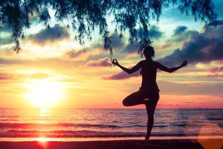 mujer meditando: El yoga y la vida sana. Muchacha de la silueta de la meditación en el fondo del mar y la puesta del sol.