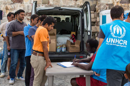 middle east crisis: KOS, GREECE - SEP 27, 2015: War refugees are registered employees of the UNHCR. Kos island is located just 4 kilometers from the Turkish coast, and refugees come from Turkey on inflatable boats.