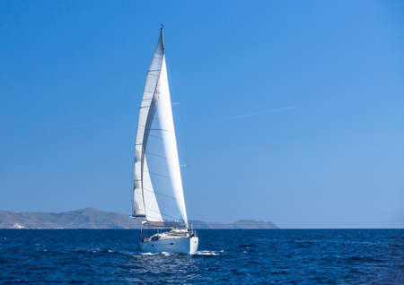 Sailing in the wind through the waves at the Aegean Sea. Yachting.