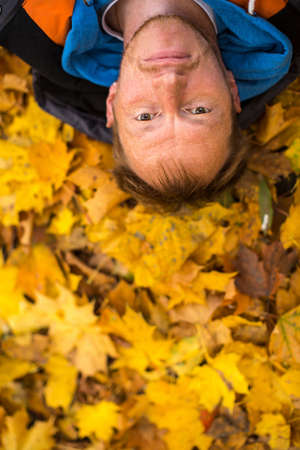 lying on leaves: Young man lying on yellow leaves.