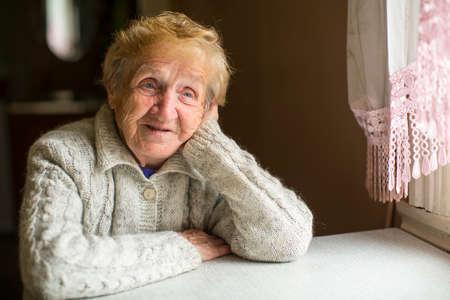 창에 의해 꿈꾸 듯이 앉아있는 노인 여성.