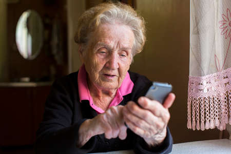 text: Elderly woman typing on the smartphone.