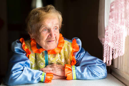 ukrainian ethnicity: Old woman in Slavic ethnic costume sits at a table near the window.