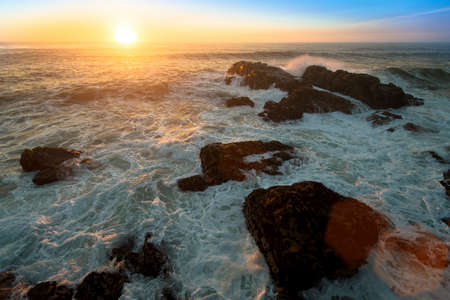 Ocean surf on the rocks during amazing sunset.