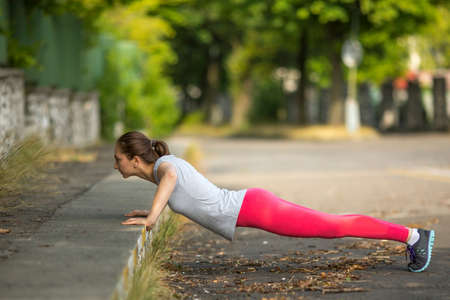 pushed: Young sports girl pushed from the land in the Park. Warm up before Jogging. Stock Photo