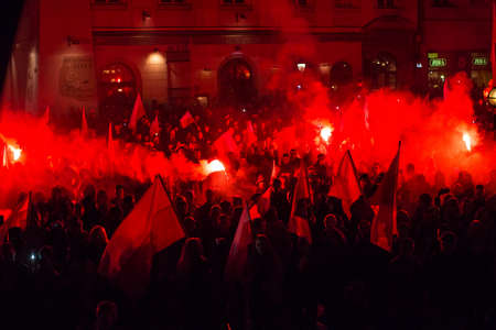 slogans: KRAKOW, POLAND - NOV 11, 2015: Protesters march through center of city. About 3.000 people took part in March of Free Poland. Participants chanted slogans Neither EU nor NATO, Poland only for Poles.