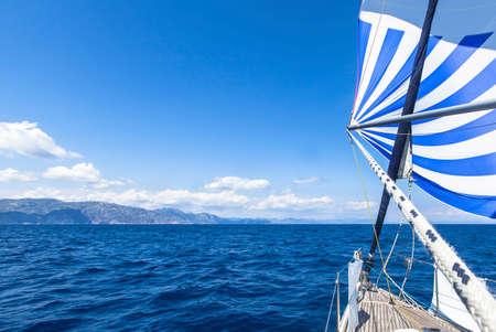 horizonte: Yates de vela de la nave con velas blancas azules en el mar. Barcos de lujo.