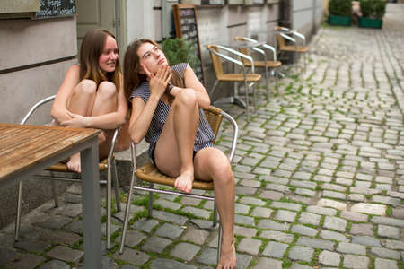 gossiping: Young girls gossiping while sitting in a street cafe. Stock Photo