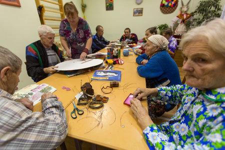 VINNITSY, Rusland - 30 november 2015: De bejaarde mensen tijdens bezigheidstherapie voor ouderen en gehandicapten in de revalidatie-afdeling in Centrum van sociale voorzieningen voor gepensioneerden en gehandicapten.