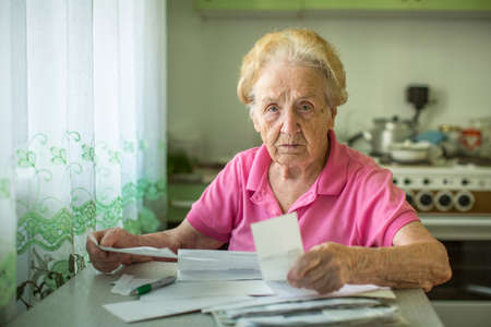 utility payments: An elderly woman writes of account for the payment of utilities.