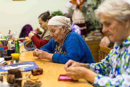 VINNITSY, RUSSIA - NOV 30, 2015: Elderly people during occupational therapy for eldery and disabled in rehabilitation department in Center of social services for pensioners and the disabled.