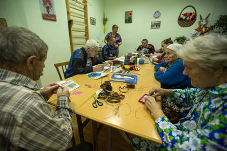 occupational therapy: VINNITSY, RUSSIA - NOV 30, 2015: Elderly people during occupational therapy for eldery and disabled in rehabilitation department in Center of social services for pensioners and the disabled.