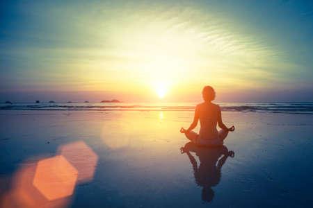 海とすばらしい夕日の背景にシルエット瞑想ヨガ女性。健康的なライフ スタイル。