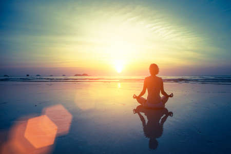 Silhouette meditation yoga woman on the background of the sea and amazing sunset. Healthy lifestyle. Archivio Fotografico