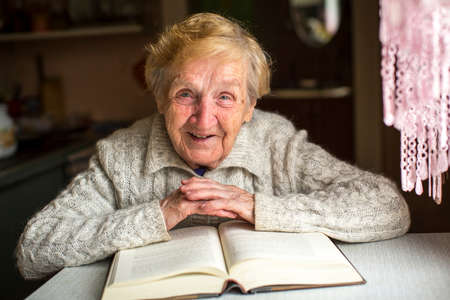 An elderly woman sits with a book at the table.