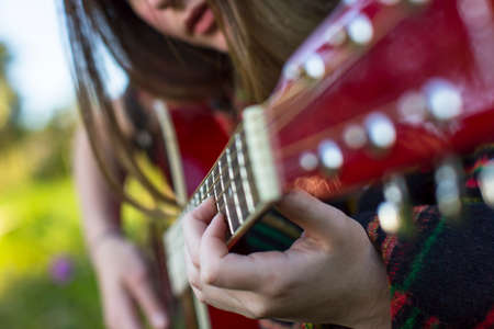 frets: Hands of a young girl on the frets of acoustic guitar.