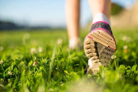 Pies corredor Primer ejecutan al aire libre en la hierba verde. Foto de archivo