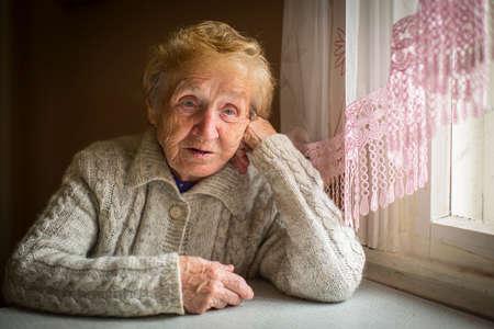 Een oudere vrouw zit alleen bij het raam. Stockfoto
