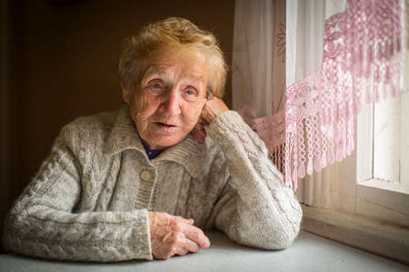 Una anciana se sienta solo cerca de la ventana.